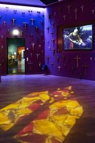 Blick in einen Raum mit vielen Kruzifixen an der Wand und einer Bildprojektion mit Darstellung der biblischen Geschichte
