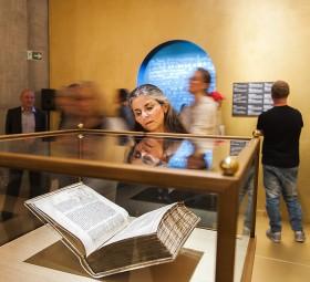 Frau vor einer Vitrine mit einem Buch, im Hintergrund andere Ausstellungsbesucher
