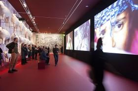 Besucher in einem Ausstellungsraum, rechts an der Wand weiße Skulpturen von Schafen, rechts eine Videoprojektion