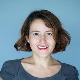 Portrait einer Frau mit braunen Haaren vor blauem Hintergrund