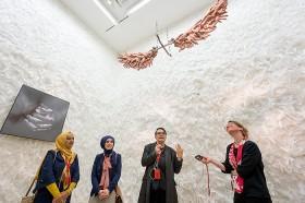 Vier Frauen stehen in einem mit weißen Federn ausgekleideten Raum, an der Decke hängt ein Kunstwerk: Flügel aus Händen