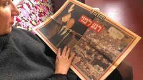 Eine Frau hält eine aufgeschlagene Zeitung in der Hand, auf der ein Bild von Yitzchak Rabin und eines von der Friedenskundgebung abgedruckt ist.