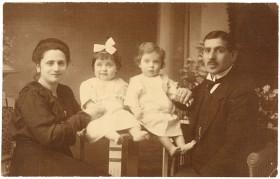 Schwarz-weiß Fotografie: Links sitzt eine Frau in dunklem Kleid, rechts ein Mann im Anzug. Zwischen ihnen sitzen auf einem Tisch zwei Kleidkinder in hellen Kleidern.