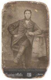 Schwarz-weiß Fotografie eines Mannes in Gehrock und Stiefeln, der an einem Tisch sitzt