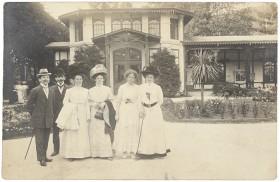 Schwarz-weiß Fotografie: Zwei Männer im Anzug und mit Hut und vier Frauen in hellen Kleidern stehen in einem Garten vor einem Haus