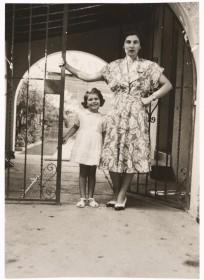 Schwarz-weiß Fotografie: Eine Frau im Kleid und ein siebenjähriges Mädchen stehen an einem Gittertor