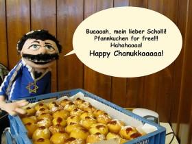 Eine Puppe in blauem Shirt mit Davidstern vor einer Kiste mit Berliner Pfannkuchen und mit einer Sprechblase: »Buaah, mein lieber Scholli! Pfannkuchen for free!!! Hahahaaaa! Happy Chanukkaaaaa!«