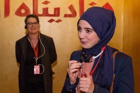 Eine Frau mit kurzen Haaren steht links im Hintergrund, im Vordergrund eine Frau mit blauem Kopftuch, die in ein Mikrofon spricht