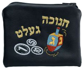 Ein schwarzer Geldbeutel, auf den ein Dreidel, Münzen und in hebräischen Buchstaben das jiddische Wort »Chanukka-Gelt« gestickt ist.