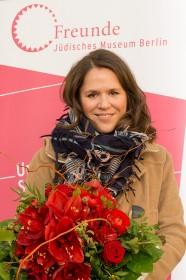 Portrait einer jungen Frau mit Blumenstrauß in der Hand, im Hingrund das Logo der Freunde des Jüdischen Museums Berlin