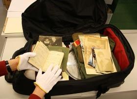 Geöffneter Koffer, in dem verschiedene Dokumente und Fotografien liegen