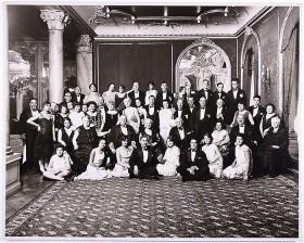 Schwarz-weiß Fotografie con etwa 50 festlich gekleideten Personen in einem prunkvollen Saal