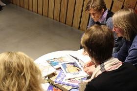 Vier Frauen sitzen um einen Tisch, auf dem mehrere Bücher liegen