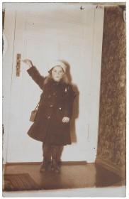 Schwarz-weiß Fotografie eines Mädchens, das an einer Tür steht