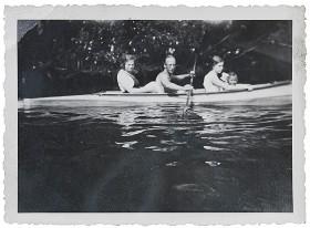 Schwarz-weiß Fotografie von einem Mann, zwei Frauen und einem Mädchen in einem Kayak