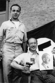 Schwarz-weiß-Fotografie zweier junger Männer, von denen einer eine Pistole und ein Hitler-Bild in den Händen hält, im Hintergrund eine großteils verdeckte Hakenkreuz-Flagge