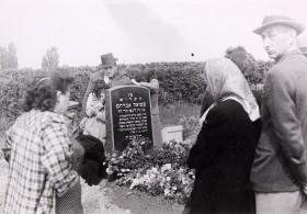 Schwarz-Weiß-Fotografie von Menschen an einem Grab mit Blumen