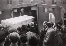 Schwarz-Weiß-Fotografie von einem Sarg, der in einen Wagen verladen wird