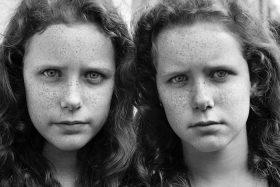 Schwarz-weiß Portrait von Zwillingsmädchen mit langen Haaren und Sommersprossen