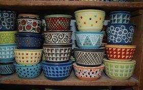 Bunt bemalte Keramikschüsseln in einem Holzregal