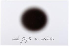 """Postkarte mit einem schwarzen Kreis auf weißem Untergund und der Unterschrift """"Liebe Grüße aus Namibia"""""""