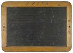 Eine schwarze Tafel mit Holzrahmen, auf dem K. ARON steht.