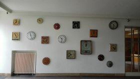 Eingangsbereich mit einer Wand voller Uhren.