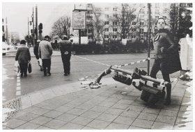Ein »Superman« steht neben einer umgetretenen Ampel an einer Straße