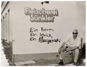 Ein Mann mit Bierflasche in der Hand sitzt vor einer Wand mit der Aufschrift »Fleischerei Sünkler« und dem Graffiti »Ein Baum, ein Strick, ein Nazigenick«