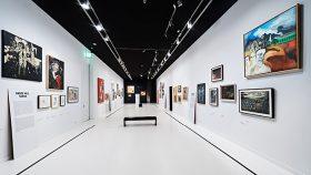 Ein Raum mit schwarzer Decke und weißen Wänden, an denen Ölgemälde und Collagen hängen