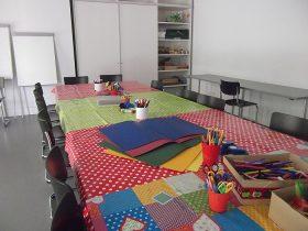 Tisch mit bunten Tischdecken und Workshopmaterial
