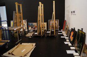 Gemälde lehnen an der Wand und stehen auf Staffeleien