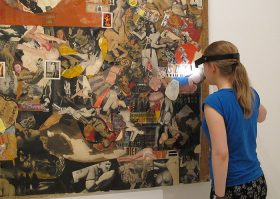 Alicija Steczek mit Stirnlampe vor einer Collage von Boris Lurie