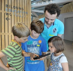 David Studniberg schaut mit zwei Jungen und einem Mädchen auf ein iPad