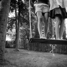 Schwarzweiß Fotografie mit den Beinen von zwei Frauen auf einer Schaukel, im Hintergrund ein Mann