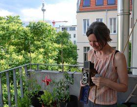 Birgit Glatzel steht mit ihrer Rolleiflex-Kamera auf ihrem Balkon