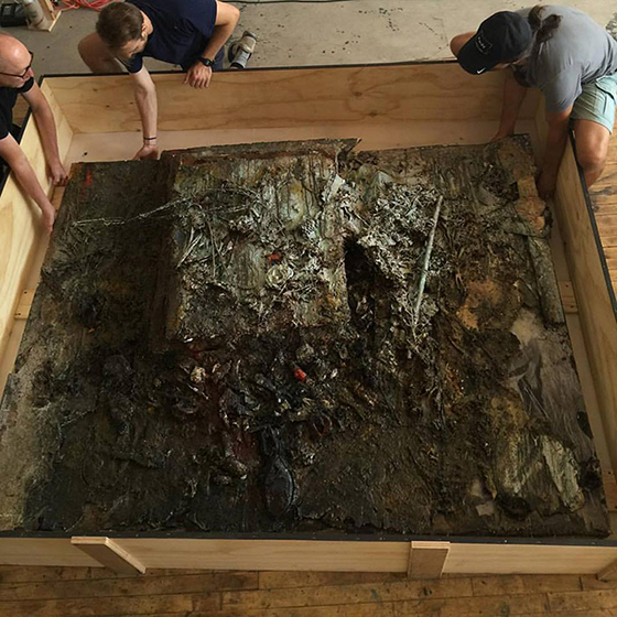 Drei Männer beginnen, ein Kunstwerk aus einer Kiste zu heben