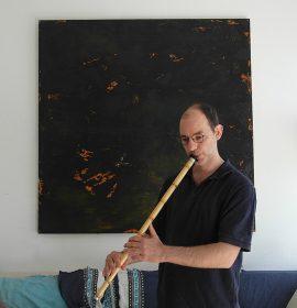 David Benforado mit einer Nay-Flöte vor einem abstrakten Gemälde