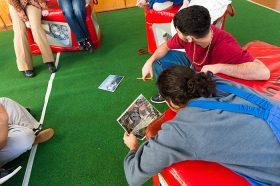 Häftlinge sitzen oder liegen auf Sitzwürfeln und schauen sich Fotos an