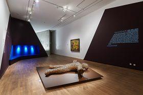 Ausstellungsraum in dessen Mitte eine überlebensgroße menschliche Figur auf dem Boden liegt