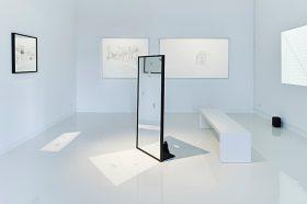 Ein weißgestrichener Raum mit Zeichnungen an den Wänden und einem Spiegel in der Raummitte