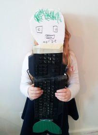 Kind hält gebastelte Fantasiefigur aus einer Tastatur mit Schwanzflosse und Papiergesicht vor sich
