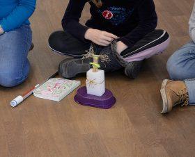 Gebastelte Fantasiefigur aus Plastik, Styropor, Stroh und anderen Recyclingmaterialien, dahinter ein Kind im Schneidersitz
