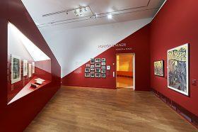 Ausstellungsraum mit roten Wänden, an denen Bilder hängen oder in die Vitrinen eingelassen sind