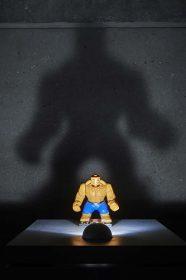 Nahansicht einer Golem-Action-Figur, die einen bedrohlichen Schatten an die Wand hinter ihr wirft