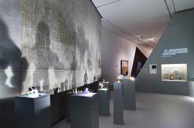 Ausstellungsraum mit Golem-Actionfiguren, die auf Sockeln stehen und Schatten an die Wand werfen