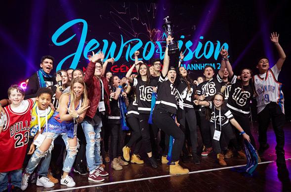 Jugendliche stehen auf der Bühne und halten Siegerpokal in die Höhe