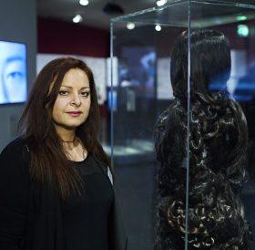 Frau steht neben einer Virtrine, in der sich eine Skulptur aus Haaren befindet