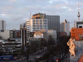 Fotografie: Im Hintergrund das Springer-Hochhaus und der Fernsehturm, im Vordergrund eine Figur auf dem Dach des Altbaus des Jüdischen Museums Berlin
