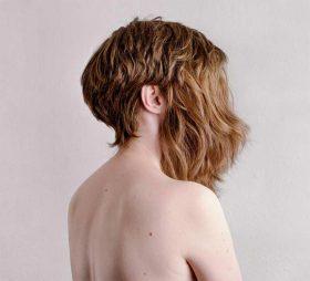 Frau mit nacktem Rücken. Steht leicht im Profil da. Gesicht von Haaren verdeckt.